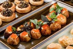 Heerlijke voorgerechten Aardappel in de schil met kaas en rode die kaviaar met basilicum op banketlijst wordt verfraaid Gastronom stock foto's