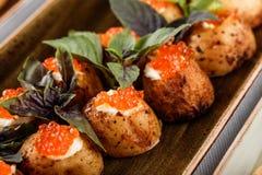 Heerlijke voorgerechten Aardappel in de schil met kaas en rode kaviaar die met basilicum op banketlijst wordt verfraaid Gastronom royalty-vrije stock foto