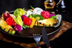 Heerlijke warme geroosterde groentensalade met avocado op restaurantachtergrond Gezond exclusief voedsel op grote zwarte stock afbeelding