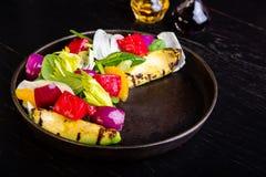 Heerlijke warme geroosterde groentensalade met avocado op restaurantachtergrond Gezond exclusief voedsel op grote zwarte royalty-vrije stock afbeeldingen