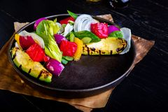 Heerlijke warme geroosterde groentensalade met avocado op restaurantachtergrond Gezond exclusief voedsel op grote zwarte stock fotografie
