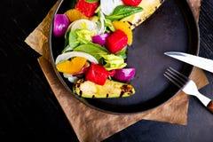 Heerlijke warme geroosterde groentensalade met avocado op restaurantachtergrond Gezond exclusief voedsel op grote zwarte stock foto