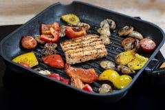 Heerlijke zalm en groenten op de grill Close-up bij het roosteren van vierkante vormzalm, rode en gele peper, kersentomaten stock foto's
