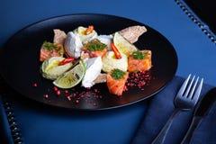 Heerlijke zalm met pastei en hummus op restaurantachtergrond Gezond exclusief voedsel op grote zwarte schotelclose-up stock afbeelding