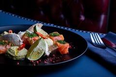 Heerlijke zalm met pastei en hummus op restaurantachtergrond Gezond exclusief voedsel op grote zwarte schotelclose-up stock fotografie