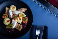 Heerlijke zalm met pastei en hummus op restaurantachtergrond Gezond exclusief voedsel op grote zwarte schotelclose-up royalty-vrije stock foto