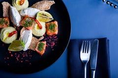 Heerlijke zalm met pastei en hummus op restaurantachtergrond Gezond exclusief voedsel op grote zwarte schotelclose-up royalty-vrije stock afbeelding