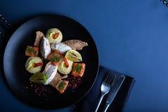 Heerlijke zalm met pastei en hummus op restaurantachtergrond Gezond exclusief voedsel op grote zwarte schotelclose-up stock foto's
