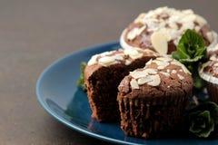 Heerlijke, zoete chocolademuffins, met amandelbloemblaadjes naast munt en amandel in een plaat op een donkere lijst royalty-vrije stock afbeelding