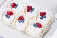 Heerlijke zoete cupcakes met room en bessen stock afbeelding