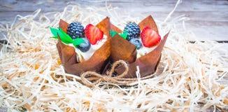 Heerlijke, zoete die cupcakes met room, chocoladeroom, kaneel, cacao wordt verfraaid verfraaid met vers, natuurlijk, organisch fr Stock Foto