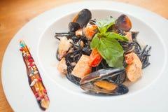 Heerlijke zwarte spaghetti Neri met roomsaus en zeevruchten stock foto's