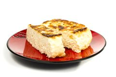 Сheese casserole. On a red plate to cut off a piece on a white background Royalty Free Stock Images