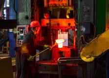 Heet die ijzer in smeltery door een arbeider wordt gehouden stock fotografie