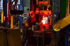 Heet die ijzer in smeltery door een arbeider wordt gehouden royalty-vrije stock afbeeldingen