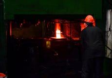 Heet die ijzer in smeltery door een arbeider wordt gehouden royalty-vrije stock afbeelding
