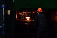 Heet die ijzer in smeltery door een arbeider wordt gehouden stock afbeelding
