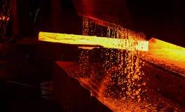Heet die ijzer in smeltery door een arbeider wordt gehouden Het smelten van metaal in een staalfabriek stock foto