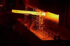 Heet die ijzer in smeltery door een arbeider wordt gehouden Het smelten van metaal in een staalfabriek stock afbeeldingen
