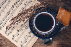 Heet drank en koekje met muzieknoten en de herfstbladeren op een houten lijstoppervlakte Hoogste mening royalty-vrije stock afbeeldingen