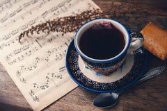 Heet drank en koekje met muzieknoten en de herfstbladeren op een houten lijstoppervlakte Hoogste mening royalty-vrije stock fotografie