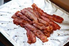 Heet heerlijk vers gekookt geroosterd varkensvleesbacon klaar om op aluminiumfolie te eten Gezonde en hartelijke olie gebraden vl royalty-vrije stock foto's