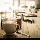 Heet koffie en giftvakje op houten lijst Stock Afbeeldingen