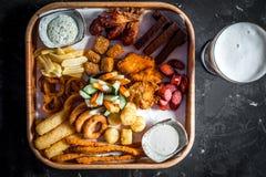 Heet lapje vlees met tomaten, salade, courgette, greens en saus op een houten raad Twee glazen donker bier Bierlijst in restaura stock fotografie