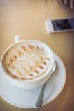 Heet van koffiedrank op houten lijstbar met mobiele telefoon Royalty-vrije Stock Foto's