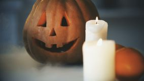 Hefboom-o-lantaarn pompoen en kaarsen op lijst met witte rook, Halloween-vooravond stock videobeelden