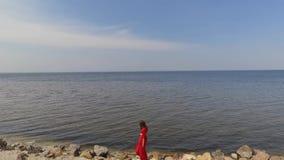 Heft de Graseful leuke jonge vrouw in rode lange kleding die handen op de grote steen dichtbij spectaculaire mening van blauwe ov stock footage