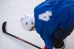Heft de spruiten van de hockeyspeler de op puck en valt stok aan stock fotografie