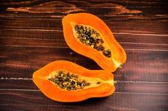 Heft zwei der frischen Papaya auf hölzernem Hintergrund lizenzfreie stockfotos