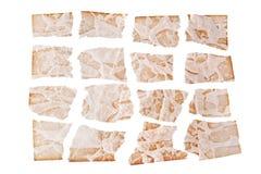 Heftige Blätter des braunen gealterten Papiers auf weißem Hintergrundabschluß oben, zackige Fetzen des alten Papierentwurfs, Kopi stockbilder