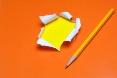 Heftiges orange Papierloch. Zerreißendes Inneregelb Stockfoto