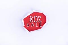 Heftiges Papier mit einem 80% VERKAUFS-Wort auf rotem Hintergrund Lizenzfreie Stockbilder
