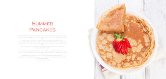 Heftklammer von goldenen Hefepfannkuchen oder -krepps des Weizens, traditionell für russische Pfannkuchenwoche, mit frischer Erdb stockfotografie