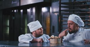 A hefty looking baker man wearing a chefs attire picks at this irresistible cake and a husky man with a beard pushing a. Large tray behind him , joins to taste stock video