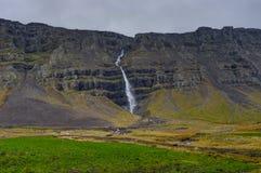 Hegifoss瀑布在有山和多云天空薄雾的冰岛 库存照片