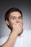 He�got a secret. Portrait of surprised young men covering his Royalty Free Stock Photography