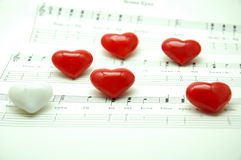 Heheart shape marbles on music note