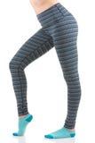 Heiße Ansicht des Passung und des sexy Frauenunterkörperteils und der -beine in bunte gestreifte Hosen und tragende blaue Socken Stockfoto