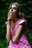 Heiße blonde Frau im rosa Kleid im Wald Stockfoto