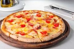 heiße Fleisch Pizza mit hamon, Käse- und Kirschtomaten auf dem hölzernen Brett auf der gedienten Restauranttabelle Lizenzfreie Stockfotografie