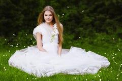 Heiße Frau auf Gras mit den Fliegenblumenblättern Stockfotos