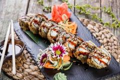 Heiße gebratene Sushirollen und maki stellten mit geräuchertem Aal-, Frischkäse, Avocado und Wasabi auf schwarzem Stein auf Bambu Stockfotografie