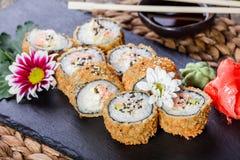 Heiße gebratene Sushirollen und maki stellten mit Krebsfleisch-, Frischkäse, Avocado und Wasabi auf schwarzem Stein auf Bambusmat Lizenzfreies Stockbild