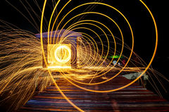 Heiße goldene Funken, die an von Mann-spinnender brennender Stahlwolle fliegen Stockfoto