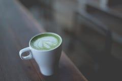 Heiße grüner Tee Lattekunst auf dem Holztisch Lizenzfreies Stockfoto