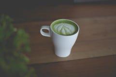 Heiße grüner Tee Lattekunst auf dem Holztisch Lizenzfreie Stockfotos
